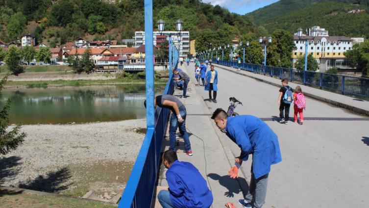 Učenici bruse i farbaju dotrajalu ogradu na mostu