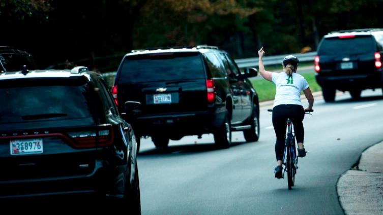 Fotografije agencije AFP: Biciklistkinja sve vrijeme držala prst u zraku dok se Tramp vozio u jednom od automobila (Foto: AFP)