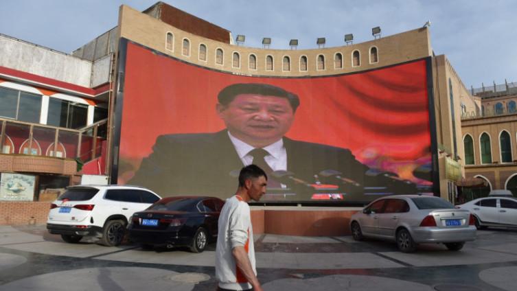 Ujgur hoda ispred platna s likom kineskom predsjednika Si Džipinga