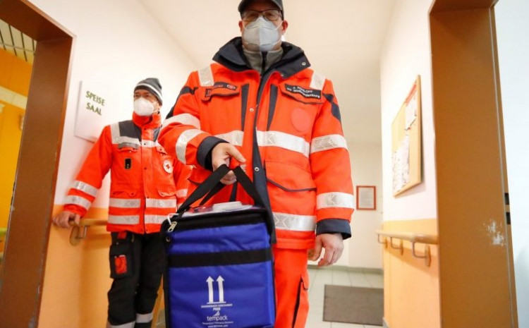 A medical worker carries a box of vials containing the Pfizer-BioNTech COVID-19, coronavirus vaccine during an inoculation program at a care home in Grossraeschen, eastern Germany , on December 27, 2020.
