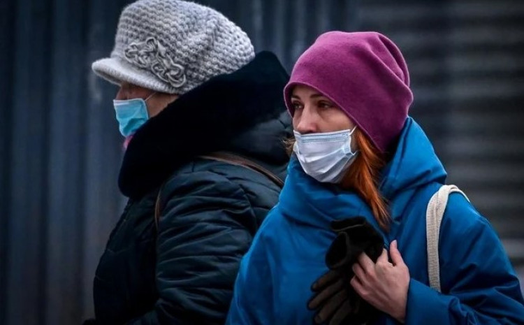 Two women wearing face masks to protect against the coronavirus disease walk along a street in central Moscow on Jan. 9, 2021.