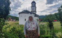 Fata Orlović in front of the church in her yard