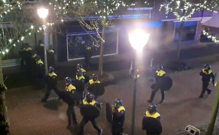 Police officers and vehicles arrive to disperse people from the site of one of the coronavirus disease (COVID-19) curfew protests in Geleen, Netherlands January 25, 2021.