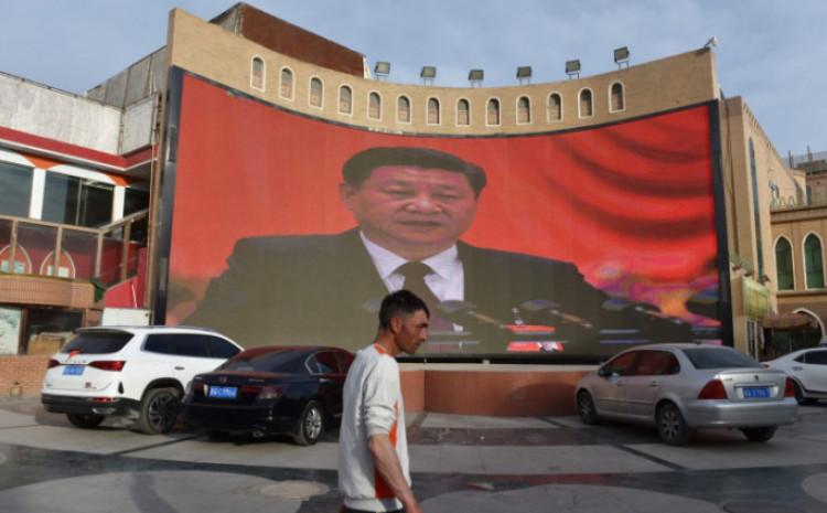 Ujgur hoda ispred platna s likom kineskog predsjednika Si Đipinga