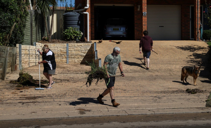 Local residents clean up debris in the aftermath of the area getting inundated with floodwaters following prolonged rains and a severe weather event in the suburb of McGraths Hill in Sydney, Australia, March 26, 2021.
