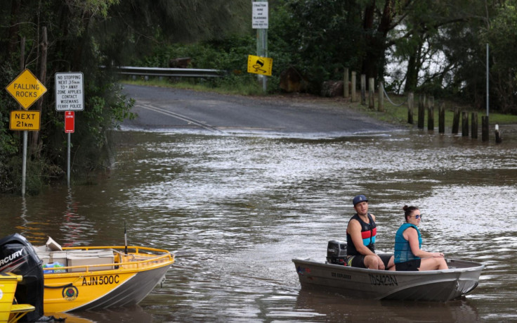 People in a boat navigate floodwaters resulting from prolonged rains northwest of Sydney in Wisemans Ferry, Australia, March 25, 2021.