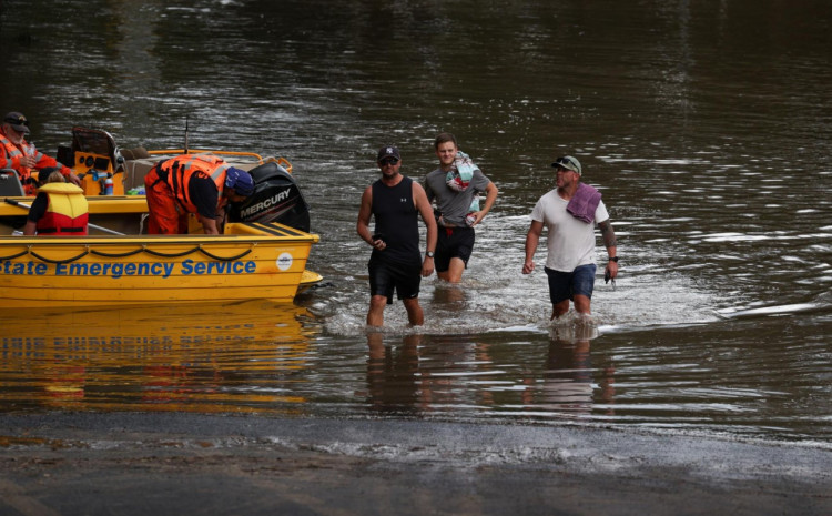 People wade through floodwaters resulting from prolonged rains northwest of Sydney in Wisemans Ferry, Australia, March 25, 2021.