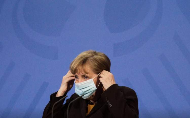 German Chancellor Angela Merkel puts on her face mask as she briefed the media after a virtual meeting with federal state governors at the chancellery in Berlin, Germany, March 30, 2021.