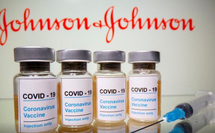 """Vials with a sticker reading, """"COVID-19 / Coronavirus vaccine / Injection only"""" and a medical syringe are seen in front of a displayed Johnson & Johnson logo in this illustration taken October 31, 2020."""