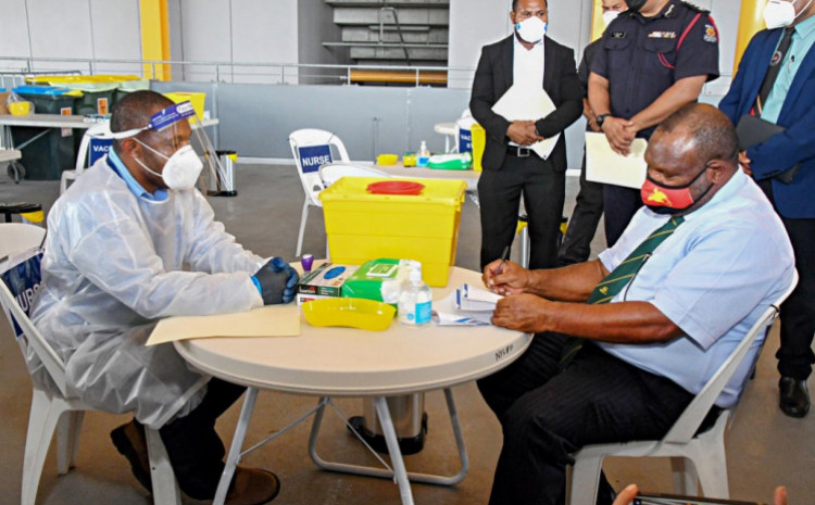 This photo taken on March 30, 2021 shows Papua New Guinea's Prime Minister James Marape (right) preparing to receive a dose of the AstraZeneca Covid-19 vaccine in Port Moresby, as Papua New Guinea's health minister on April 1 called disinformation spread on Facebook