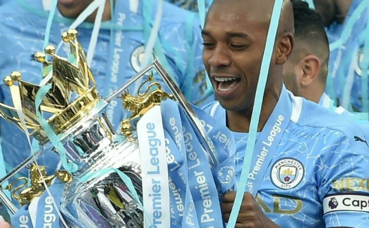 Manchester City midfielder Fernandinho lifts the Premier League trophy